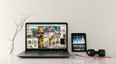 Laptop z wynajmu laptopa leży na stole wraz z tabletem, słuchawkami i wazonem