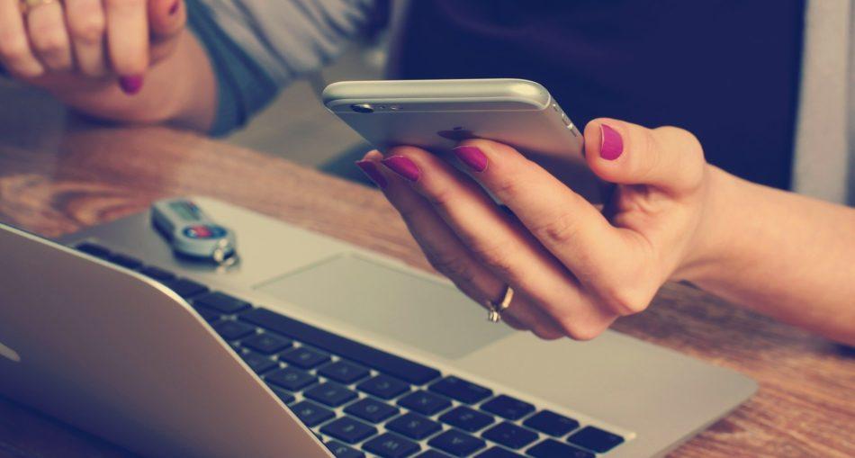 laptop z wypożyczalni laptopów; osoba siedzi przy laptopie; w ręku trzyma telefon